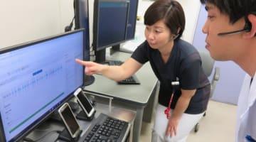 患者との会話を示した声紋と文字に変換した画面を見る医療スタッフら=横須賀共済病院
