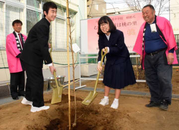 モモの木を植樹する生徒ら=川崎市中原区の西中原中学校