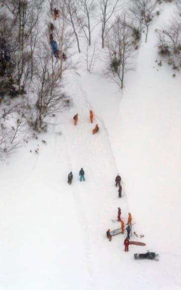 高校生らが雪崩に巻き込まれたスキー場で救助活動をする消防隊員ら=2017年3月27日