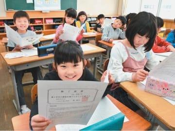 「あゆみ」で自分の成長を確かめる児童たち(画像は一部加工)=26日午前、大分市下郡小学校