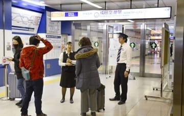 線路のレールにひびが見つかり、運転見合わせとなっていることを利用客(手前側)に伝える京成電鉄の関係者=26日午後1時9分、成田空港駅