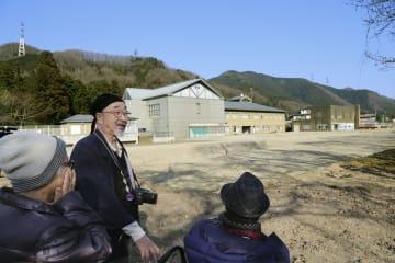 居住棟などの解体工事が終了した「津久井やまゆり園」の様子を見に来た尾野剛志さん(中央)=26日午後、相模原市