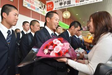 市民らから出迎えを受け、笑顔を見せる酒井淳志主将(中央)ら石岡一高の選手たち=26日午後、JR石岡駅