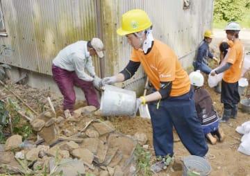 手際よく土砂やがれきを運び出す大学生=26日午前、宇和島市吉田町法花津