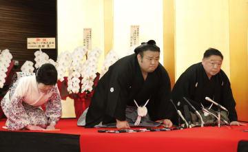大関昇進の伝達を受けた貴景勝。両隣は千賀ノ浦親方夫妻=27日午前、大阪市内のホテル