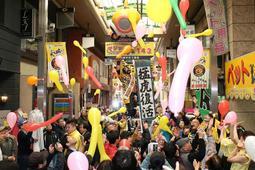 優勝マジック「143」のボードが掲げられた商店街で、ジェット風船を飛ばすファンら=27日午前、尼崎市神田中通3(撮影・風斗雅博)