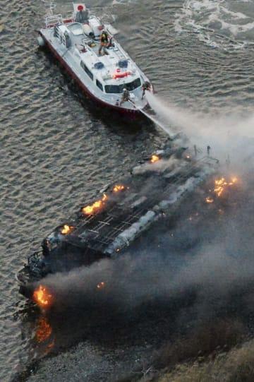 荒川で煙を上げて燃える屋形船=27日午後5時50分、東京都葛飾区(共同通信社ヘリから)