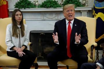 ベネズエラの野党連合出身で暫定大統領就任を宣言したグアイド国会議長の妻ファビアナさん(左)と会談するトランプ米大統領=27日、ワシントン(ロイター=共同)