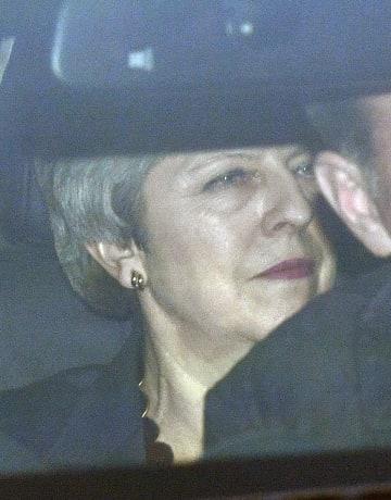 英国会議事堂を車に乗って離れるメイ首相=27日、ロンドン(AP=共同)