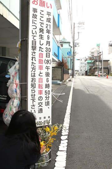 現場で花を供える小関孝徳君の母親=熊谷市