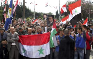 27日、シリア西部タルトスで、トランプ米大統領によるゴラン高原のイスラエル主権承認に抗議する人々(国営シリア・アラブ通信、AP=共同)