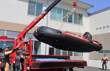 【クレーンでつり上げて車に載せられる新型ボート(27日、和歌山県串本町サンゴ台で)】