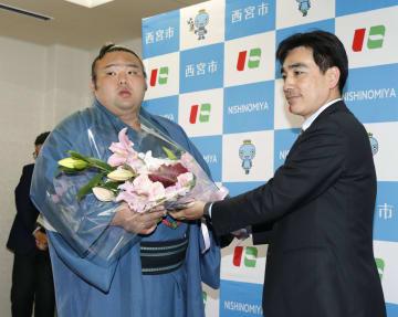 兵庫県西宮市役所を表敬訪問し、石井登志郎市長(右)から花束を受け取る貴景勝関=28日午後