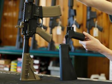 銃に取り付けて連射を可能にする特殊装置「バンプ・ストック」(右)=2017年10月、米ユタ州の銃販売店(ロイター=共同)