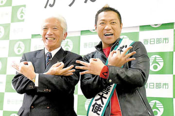 決めのポーズで笑顔を見せるはなわさん(右)と石川良三市長=春日部市役所(市提供)