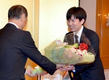 大森市長から花束を受け取る八重野さん(右)