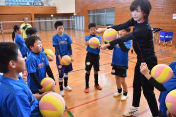 児童にパスのこつを指導する佐田さん(右)