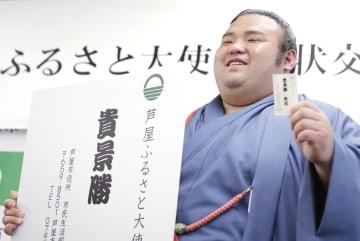 就任した「芦屋ふるさと大使」の名刺を手に笑顔の貴景勝関=29日午後、兵庫県芦屋市