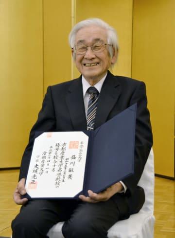 名誉教授の称号を授与され、笑顔で記念撮影に応じる京都産業大教授の益川敏英氏=29日午後、京都市
