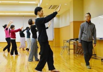 笠井(右)の指導で独特の呼吸法を練習するワークショップ参加者