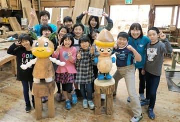 完成した鹿北町のゆるキャラ「おぐりちゃん(左)」「くりのこちゃん」の木像を囲む子どもたち=山鹿市