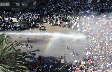 29日、アルジェリアの首都アルジェで、ブーテフリカ大統領の退陣を求めるデモ隊を鎮圧する警察=29日(ゲッティ=共同)
