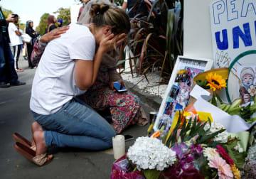 銃乱射事件発生から1週間後の3月23日、事件現場となったモスク前で座り込む女性(写真:ロイター/アフロ)