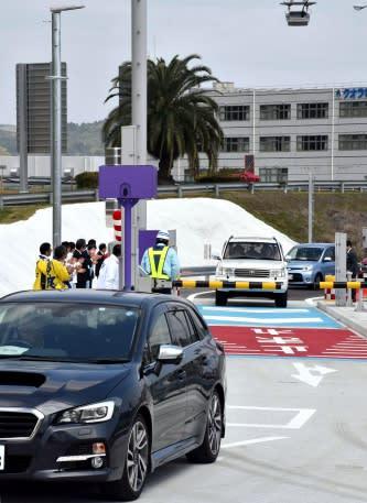 関係者に見送られ、桜島スマートインターのゲートを通過する車両=姶良市西餅田