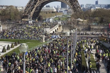 30日、パリのエッフェル塔近くを歩く黄色いベスト運動のデモ隊(共同)