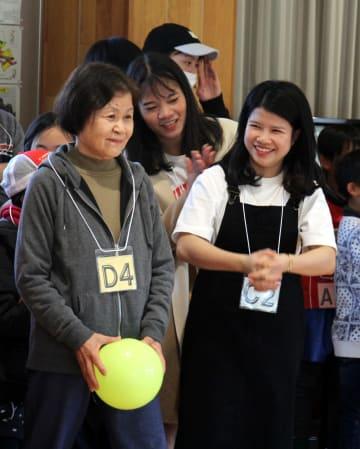 住民(左)と一緒にゲームを楽しむベトナム人技能実習生ら=長崎市、横尾地区ふれあいセンター
