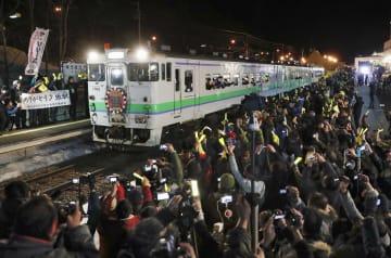 大勢の人が黄色いペンライトを振って見送る中、JR夕張駅を出発する最終列車=31日夜、北海道夕張市