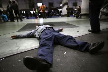 「あいりん総合センター」で閉鎖に抗議し、シャッターが閉まらないよう真下に寝転ぶ男性=31日午後、大阪市西成区