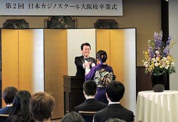卒業生に卒業証書を授与し、握手を交わす大岩根校長=31日、大阪市中央区