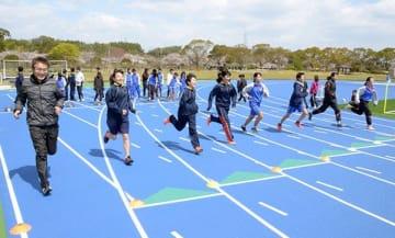 青色の舗装に生まれ変わった陸上競技場のトラックを走る子どもら=益城町