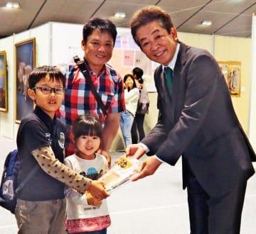 沖縄タイムスの比嘉敏幸取締役(右)から記念品を受け取る長島誠さん(中央)、航大さん(左)、菜帆さん=31日、浦添市・ANAアリーナ浦添