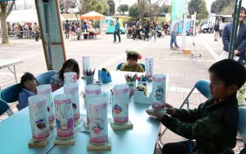 模擬店が並ぶ中、手作りの絵灯ろうを手にする子どもたち=伊勢原市の総合運動公園