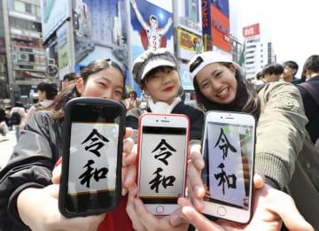 大阪・道頓堀で、新元号「令和」を画面に表示させたスマートフォンを手に笑顔の女性たち=1日午後0時15分