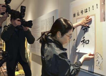 京都市の漢字ミュージアムで、新元号「令和」の漢字が書かれた紙を貼る職員=1日午後