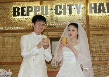 竹のコップに注いだ甘酒で乾杯する新郎新婦=別府市役所