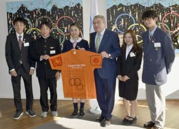 IOCのバッハ会長(左から4人目)と面会し、寄せ書きしたTシャツを手渡した岩手、宮城、福島の中高生ら。左から土佐海斗君、高野圭太郎君、佐藤葉月さん、(1人おいて)雁部みゅうさん、佐々木響君=1日、スイス・ローザンヌ(共同)