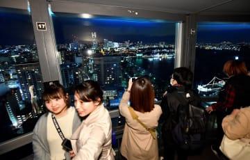 一時休館を翌日に控え、展望フロアから景色を楽しむ人たち=3月31日夜、横浜市中区の横浜マリンタワー