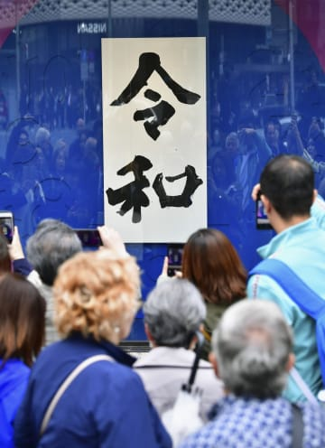 東京・銀座の「和光」に展示された、新元号「令和」の書を撮影する人たち=1日午後1時28分
