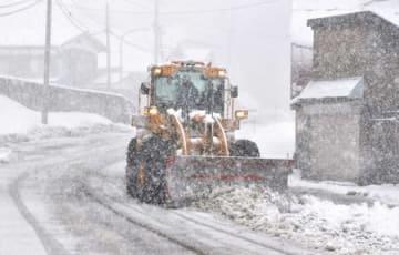 降りしきる雪の中で作業する除雪車=2日、十日町市松之山湯山