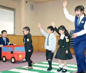 黄色いワッペンを着けて横断歩道の渡り方を学ぶ児童=鹿児島市の県警本部