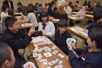 カードゲームを通してSDGsを学ぶ参加者とたかまつななさん(中央)=行方市麻生