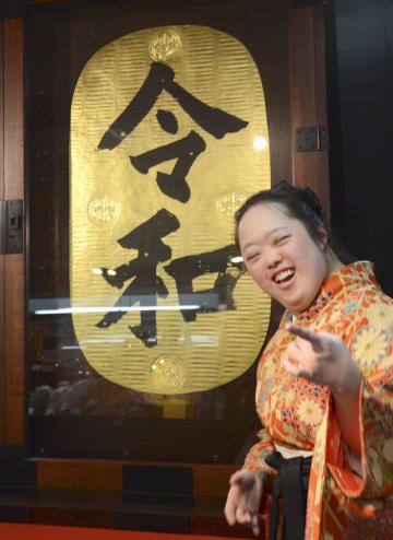 揮毫した新元号「令和」の前で笑顔の金沢翔子さん=3日午前、横浜市