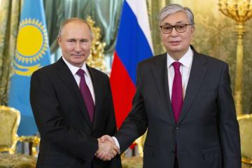 クレムリンでの会談でロシアのプーチン大統領(左)と握手を交わすカザフスタンのトカエフ大統領=3日、モスクワ(AP=共同)