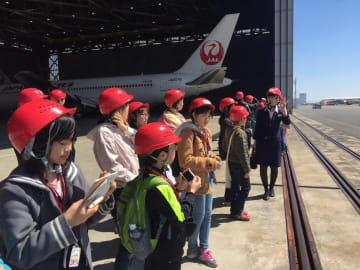 機体整備工場で日航職員から飛行機について説明を受ける豆記者=羽田空港