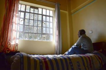ケニアの首都ナイロビ郊外のアパートで、窓の外を見つめるナマルさん=1月(共同)