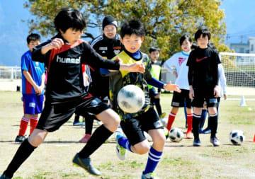 FC今治のコーチから体の使い方のアドバイスを聞き、ボールを奪い合う小学生